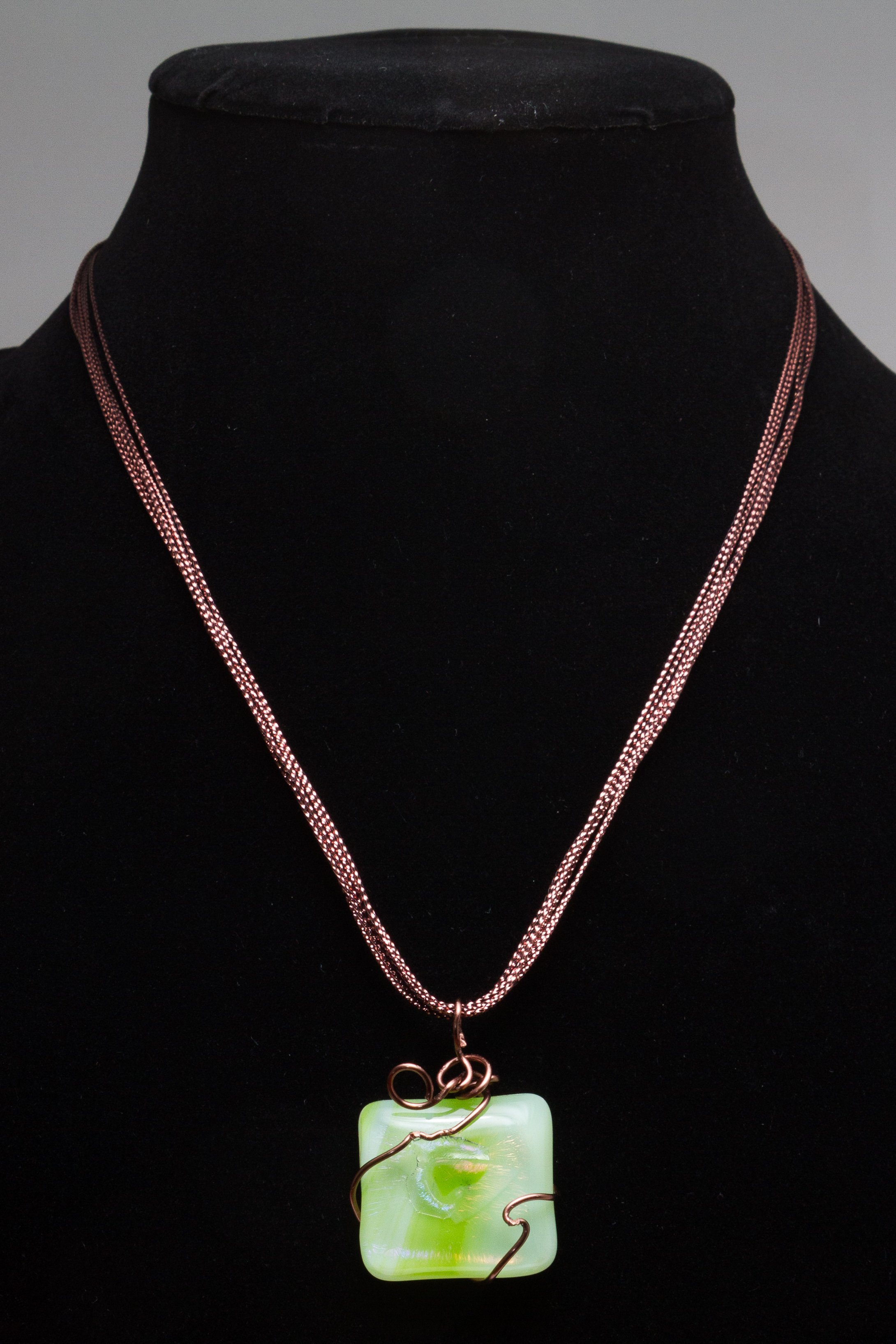 pendant made with green fused glass with copper wire wrap